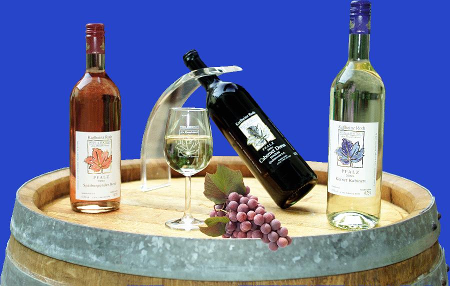 Drei Flaschen Wein, ein Glas Weißwein und rote Trauben auf einem Holzfass